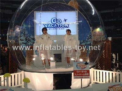 Taking photos inflatable snow globe with backdrop