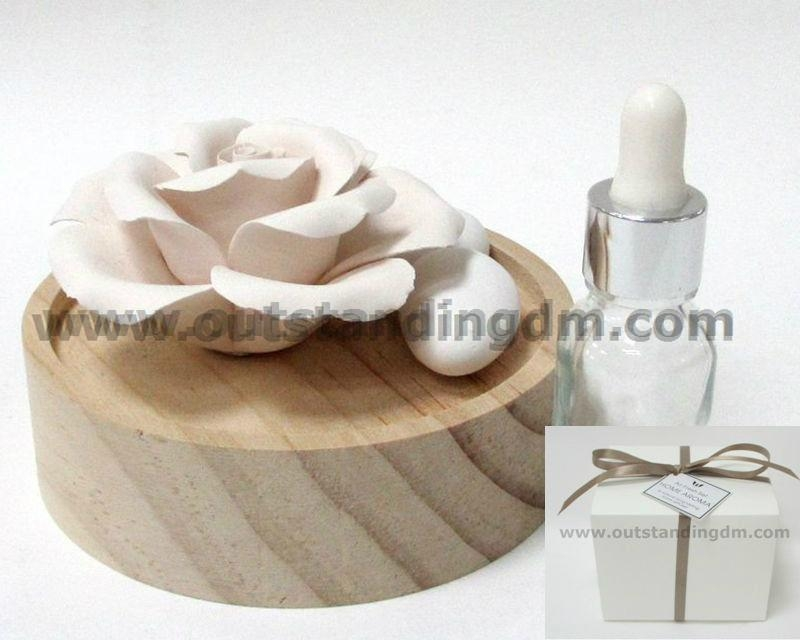 ceramic flower in wooden plate with essential oil