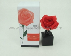 red artificial flower in black glass bottle