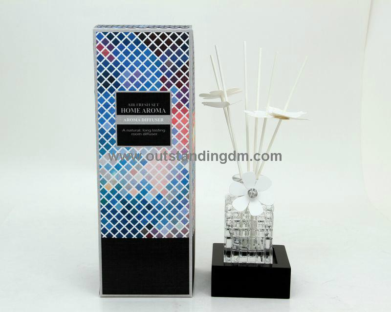 reed diffuser with  clear glass bottle with stopper and paper flower decoration on the neck of glass bottle